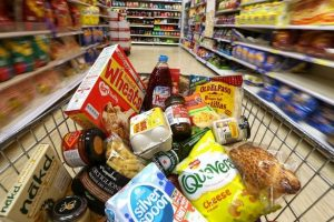 Groceries-in-a-shopping-trolley-move-through-a-food-aisle